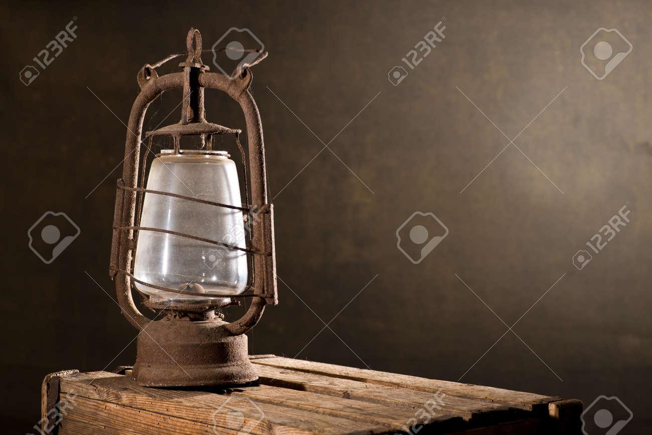Vieille lanterne rouillée sur le bureau en bois dans le grenier