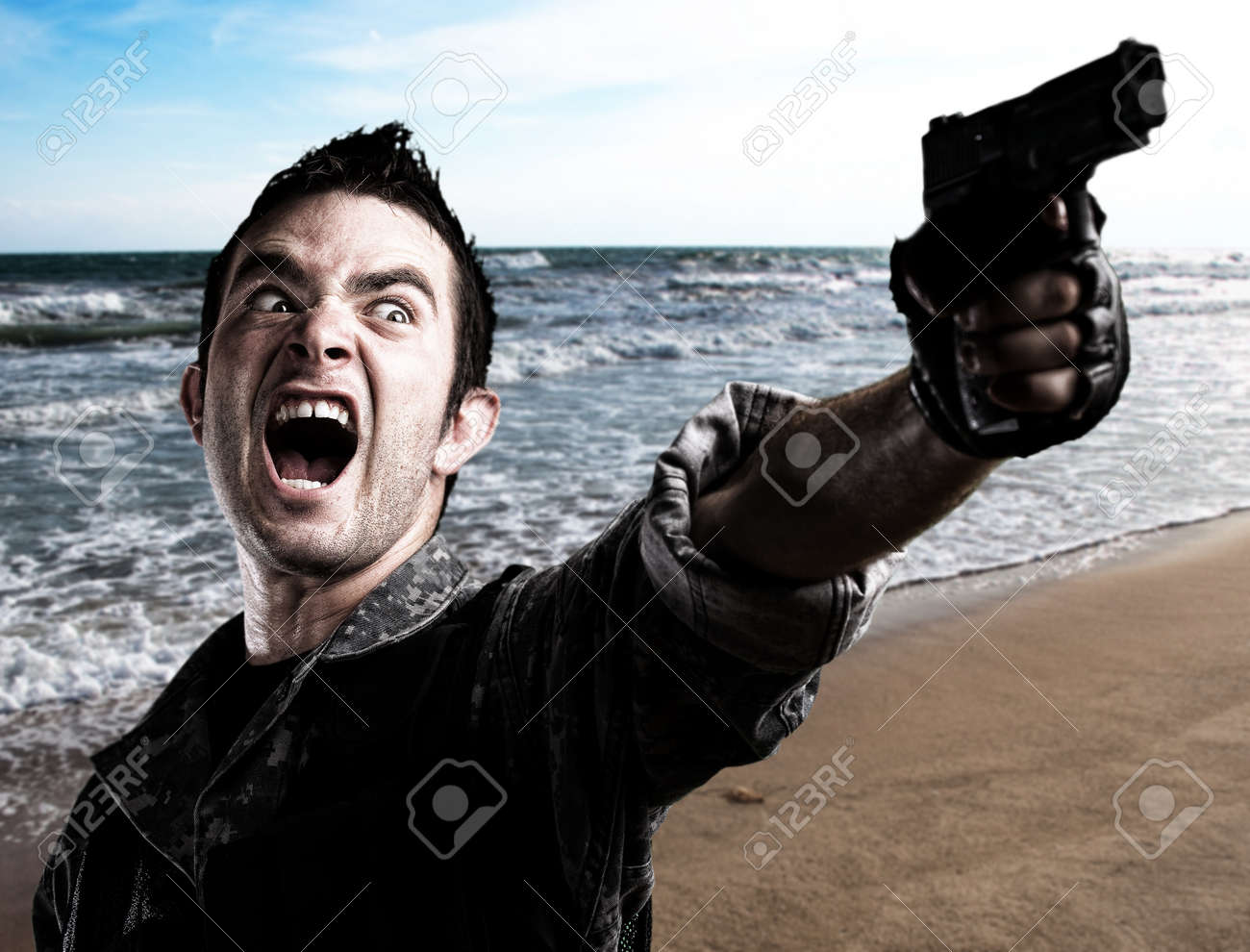 young soldier shotting with gun near the sea shore Stock Photo - 10383786