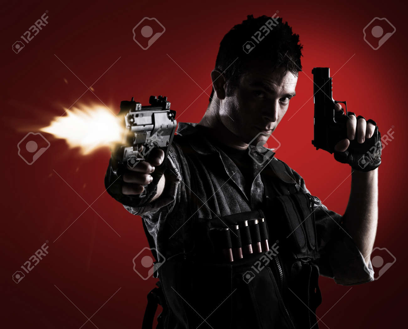 young soldier shooting with a pistol on a red background Stock Photo - 10383819