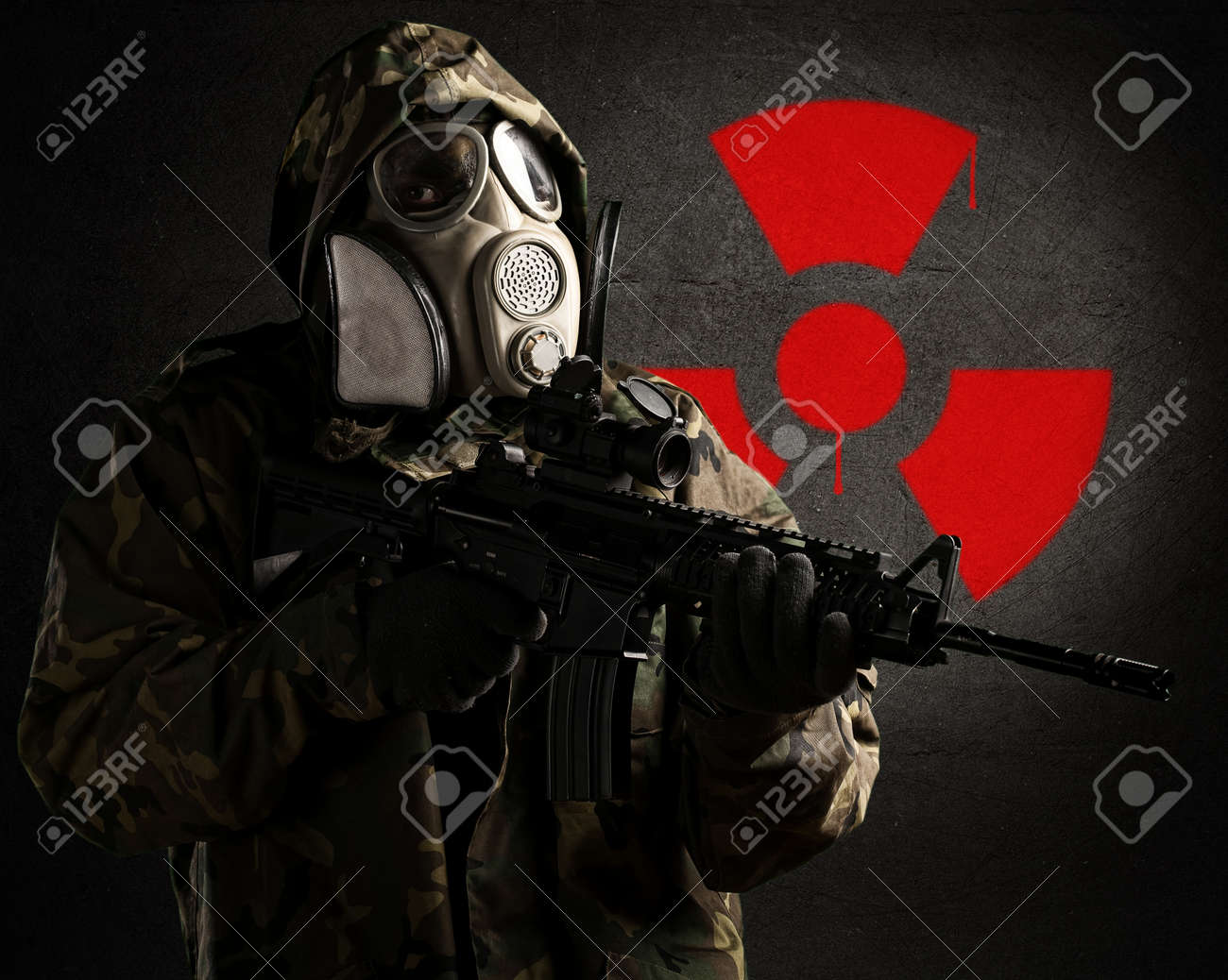 armed soldier wearing a gas mask against a concrete wall with red radioactive symbol Stock Photo - 10369692