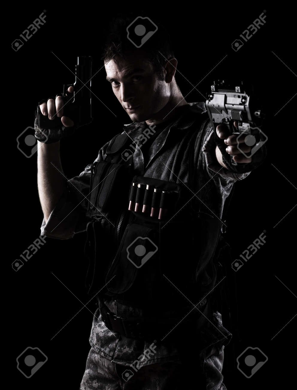 young soldier shooting with a pistol on a black background Stock Photo - 10550399