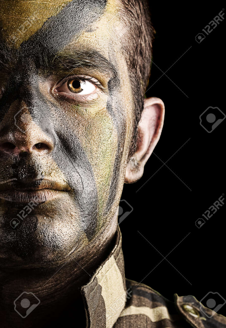 portrait of young soldier face with jungle camouflage paint against a black background Stock Photo - 10550758