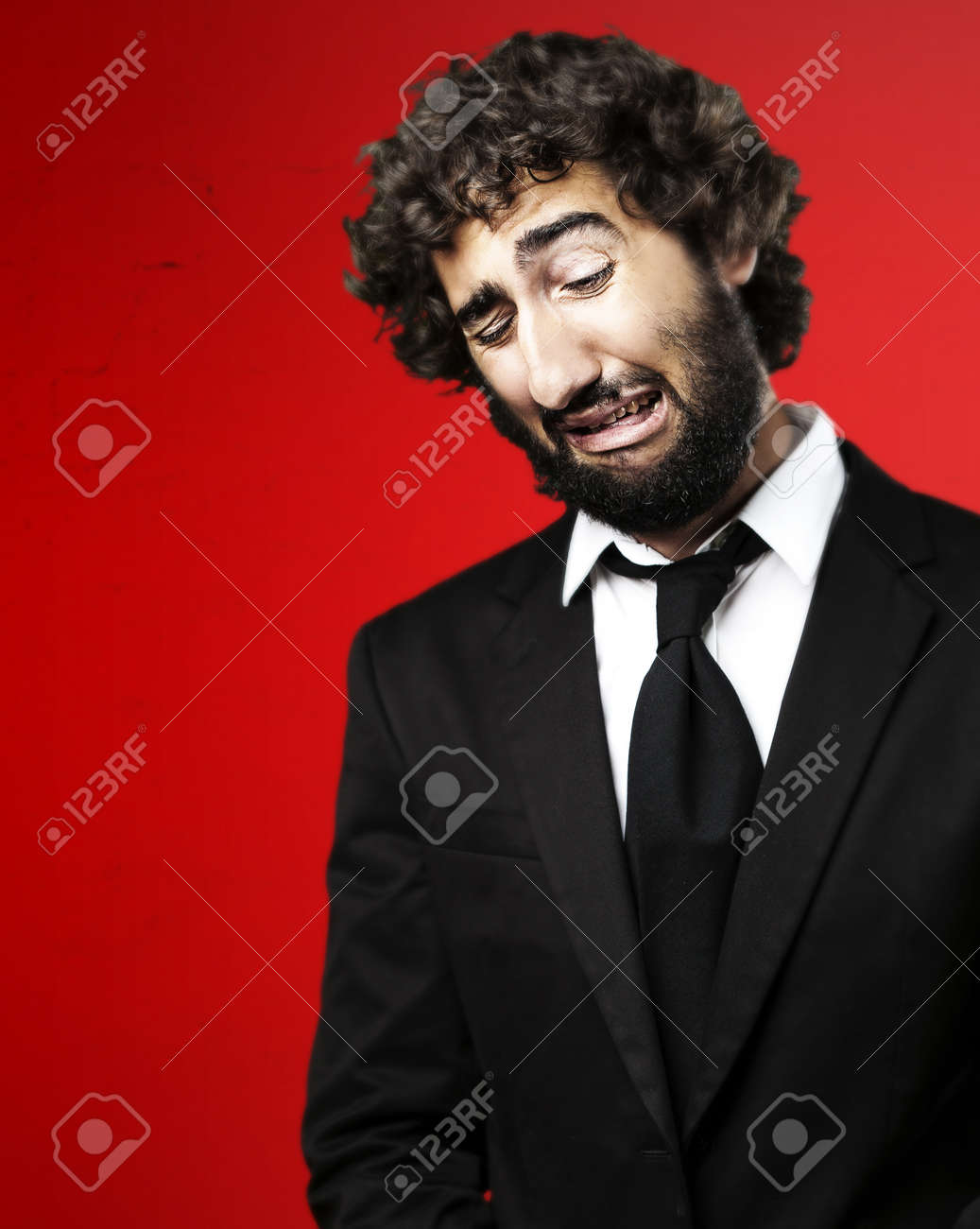 portrait of young business man with suit crying against a red background Stock Photo - 10550362