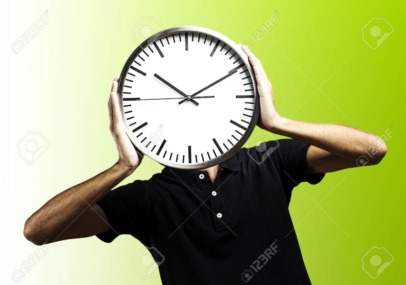 young man covering his face with a clock over green background Stock Photo - 10550368