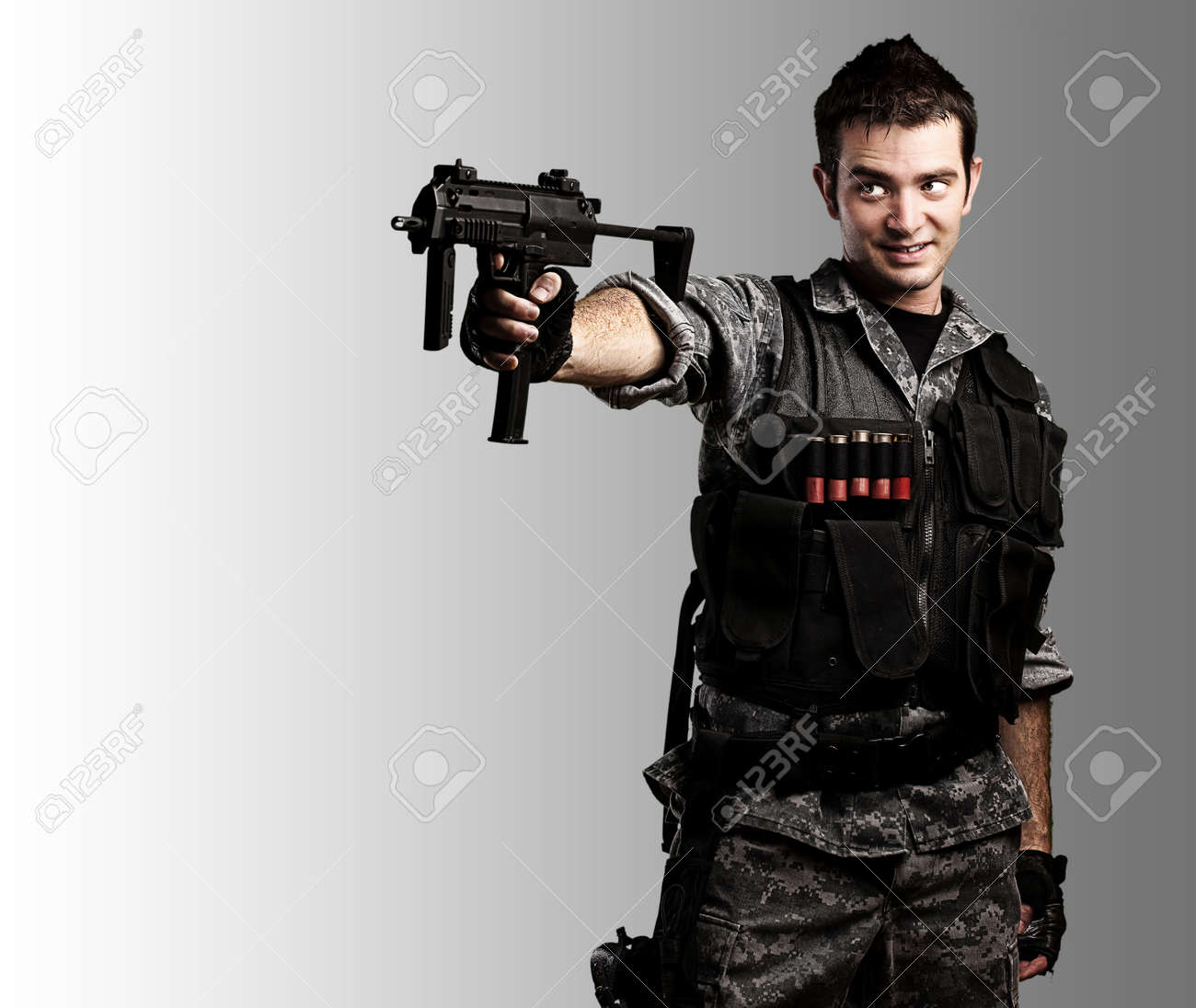 portrait of young soldier smiling with a rifle against a grey background Stock Photo - 11490048