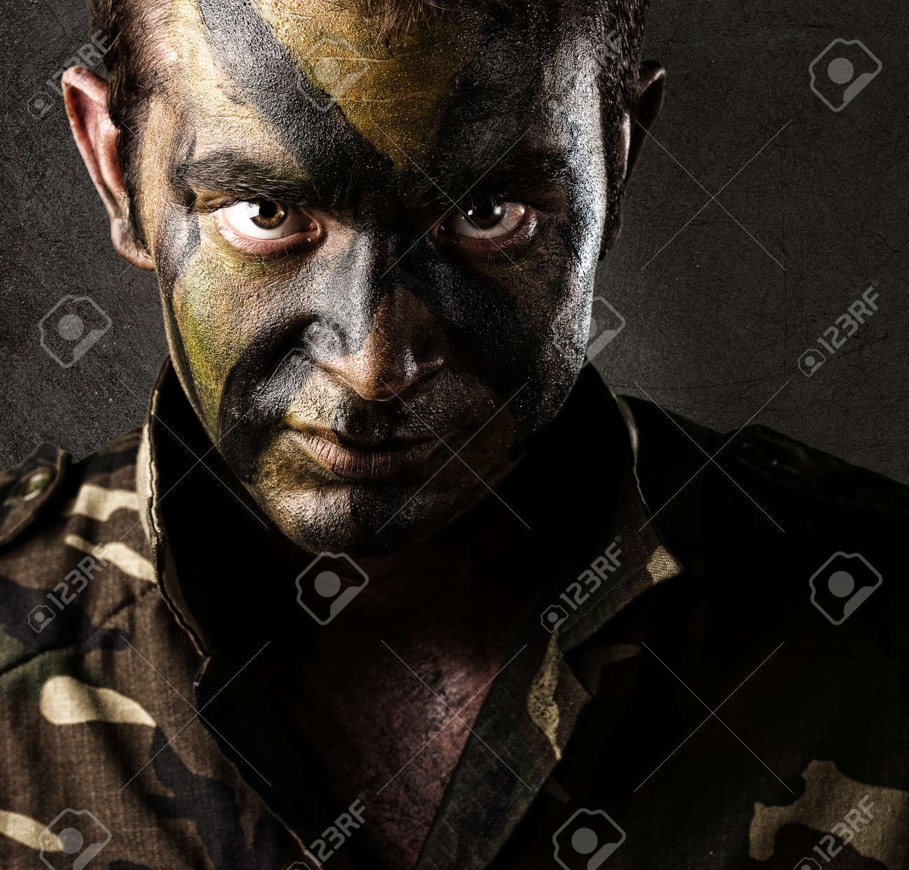 young soldier face looking straight ahead againsta a grunge wall Stock Photo - 11507700