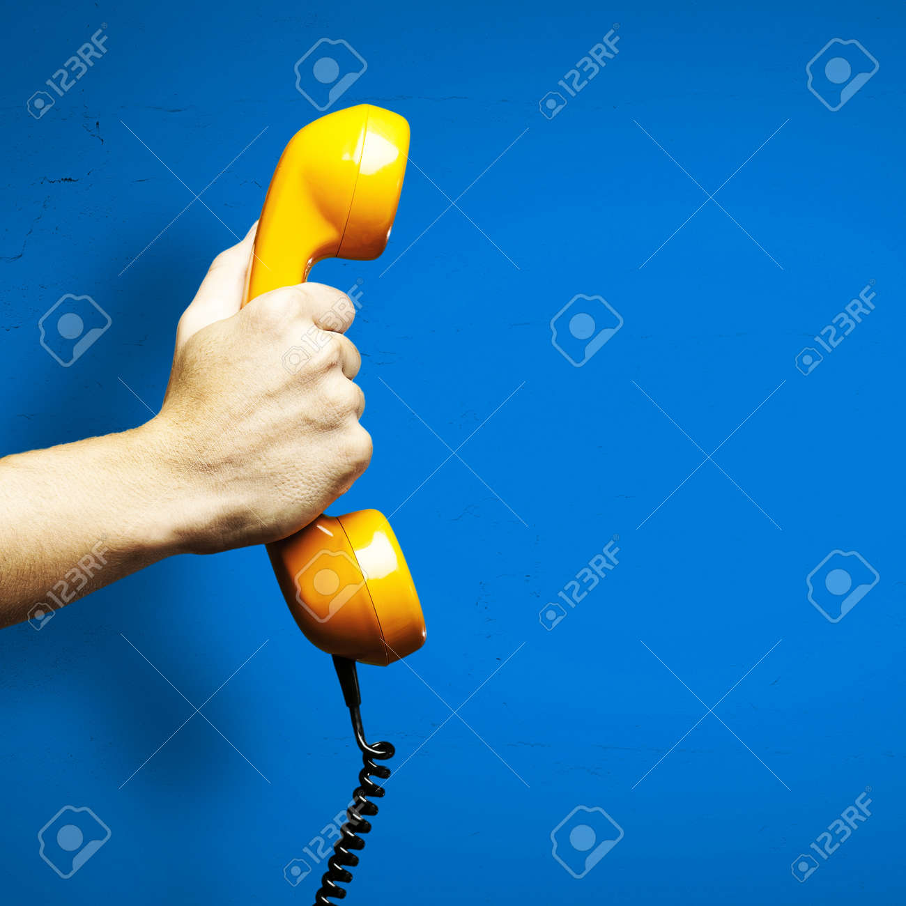 Hand holding vintage telephone receiver isolated over blue background - 11232266