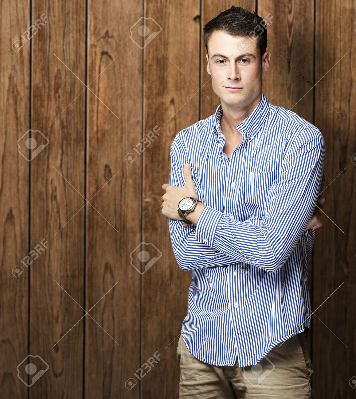 portrait of a serious young man against a wooden wall Stock Photo - 11507960