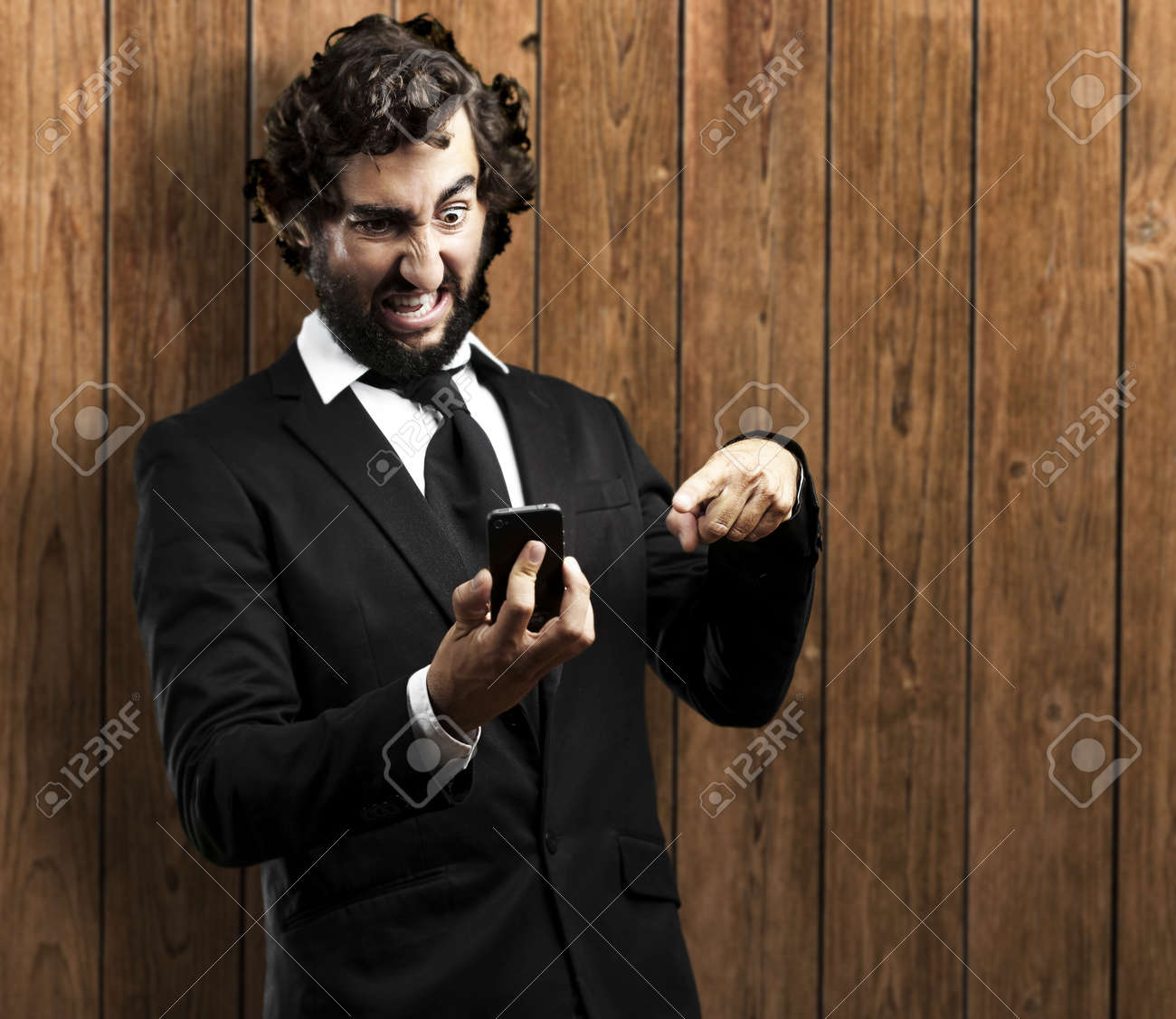 portrait of business man angry with technology against a wooden wall Stock Photo - 12105208