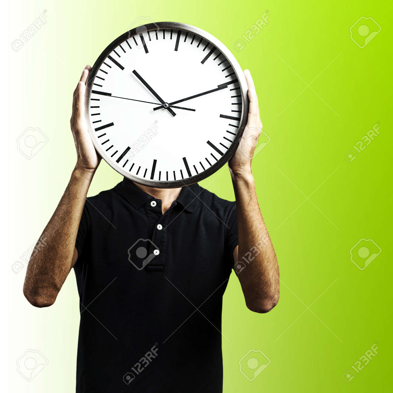 young man covering his face with a clock over green background Stock Photo - 12105531