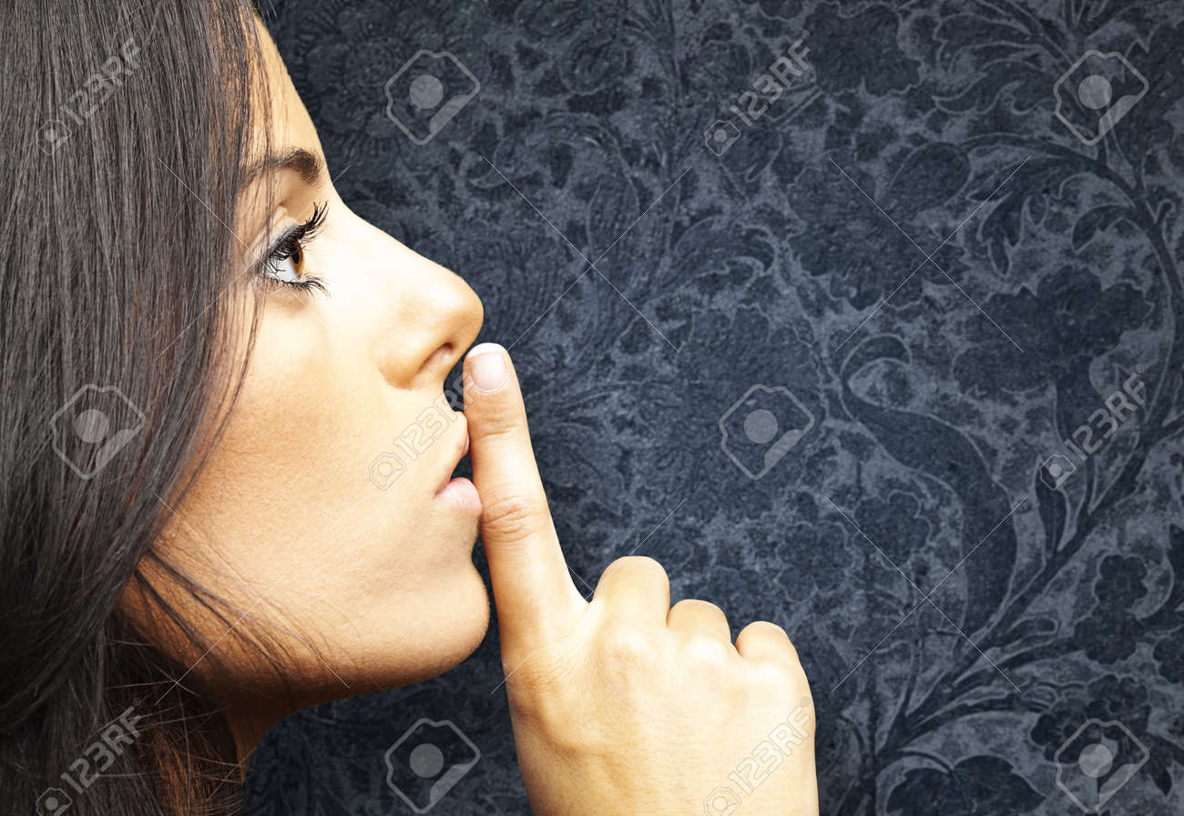 portrait of young woman doing silence sign against a vintage background Stock Photo - 12105251