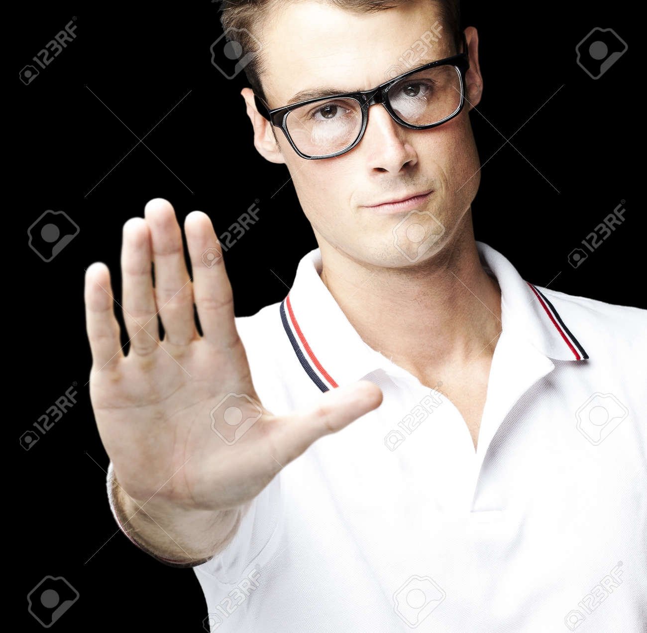 portrait of young man doing stop symbol over black background Stock Photo - 12105808