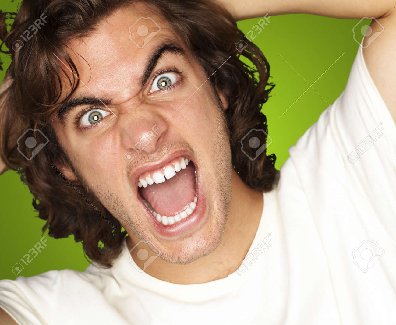 young angry man shouting against a green background Stock Photo - 13155971