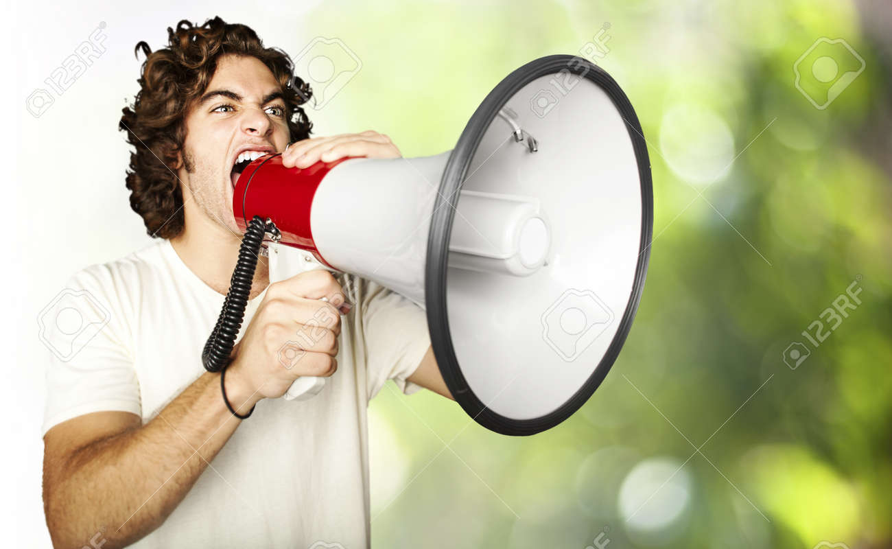portrait of young man shouting using megaphone against a nature background Stock Photo - 13156088