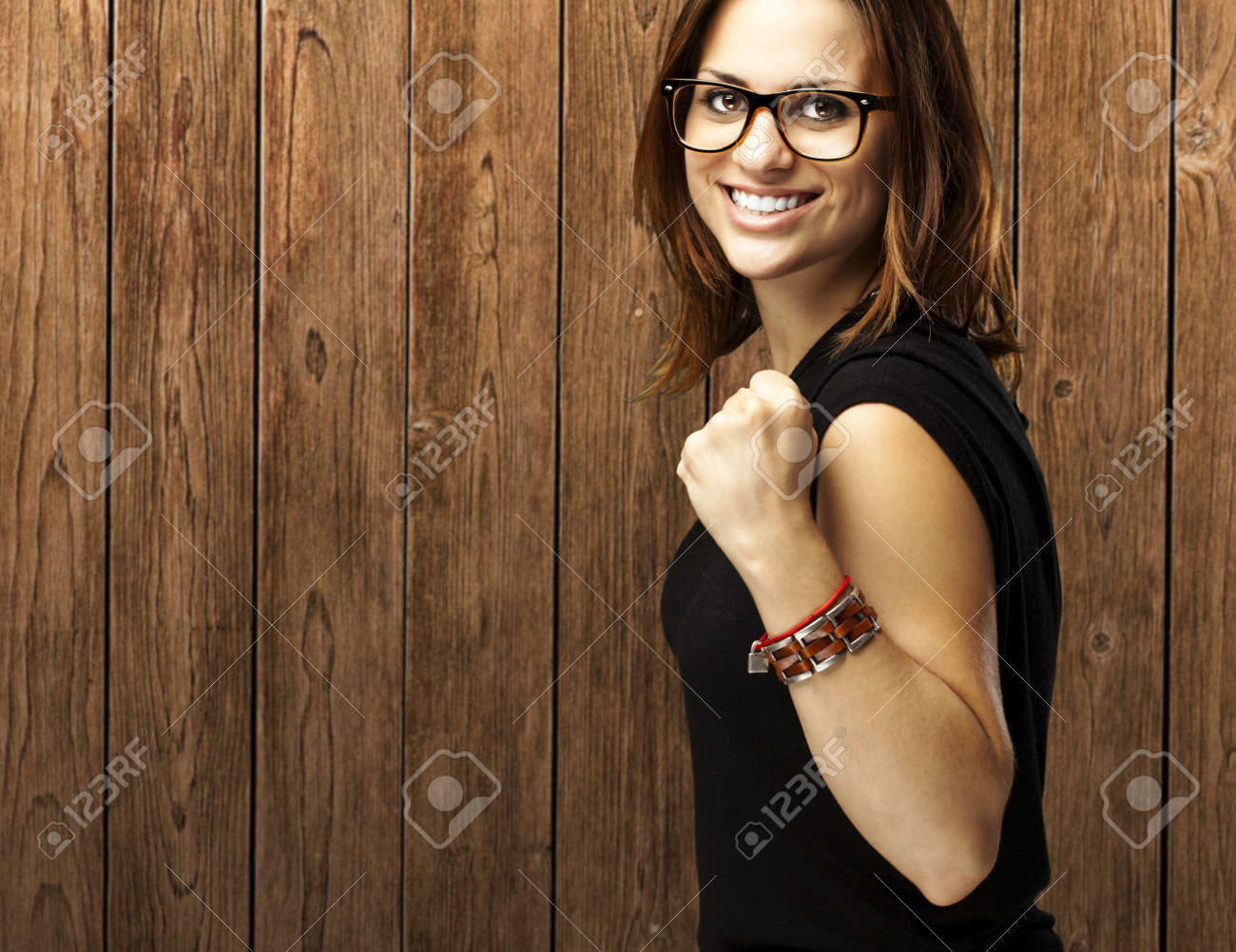 portrait of young woman win gesture against a wooden wall Stock Photo - 13156194