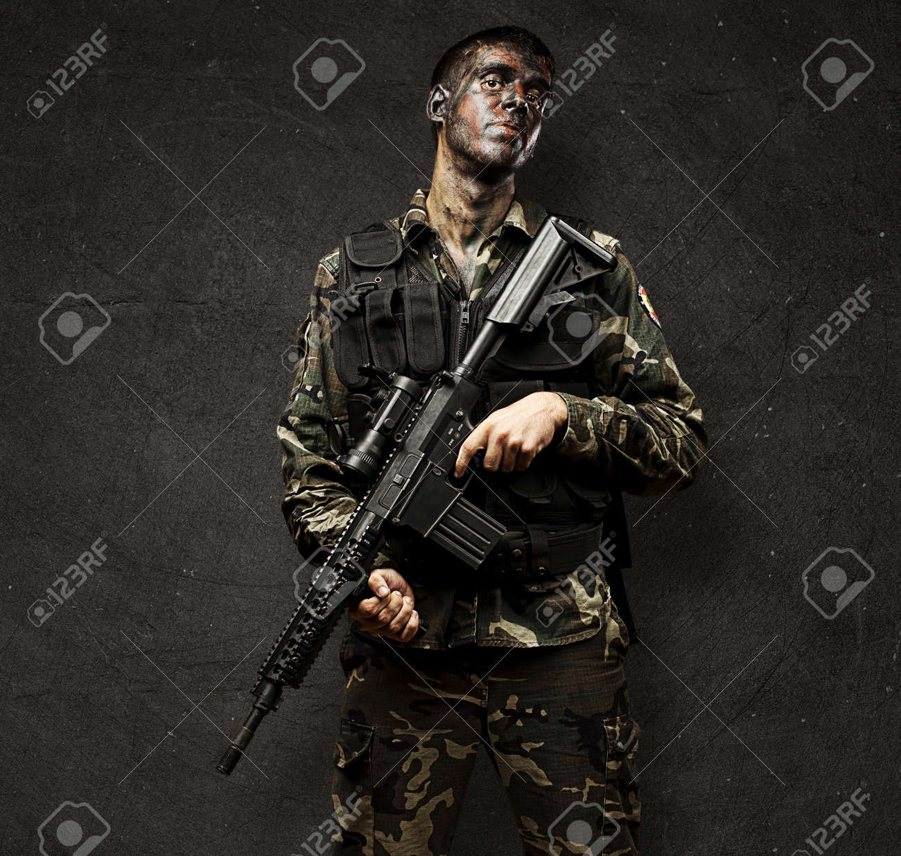 portrait of young soldier holding rifle against a grunge background Stock Photo - 13156210