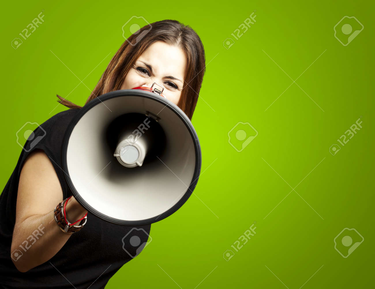 portrait of young woman shouting with megaphone over green Stock Photo - 12656144