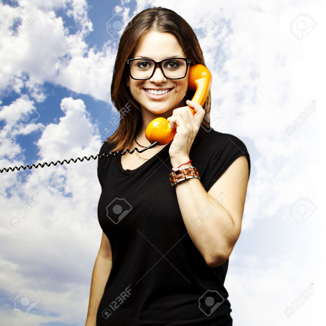 portrait of young woman talking using a vintage telephone against a blue sky background Stock Photo - 12656184
