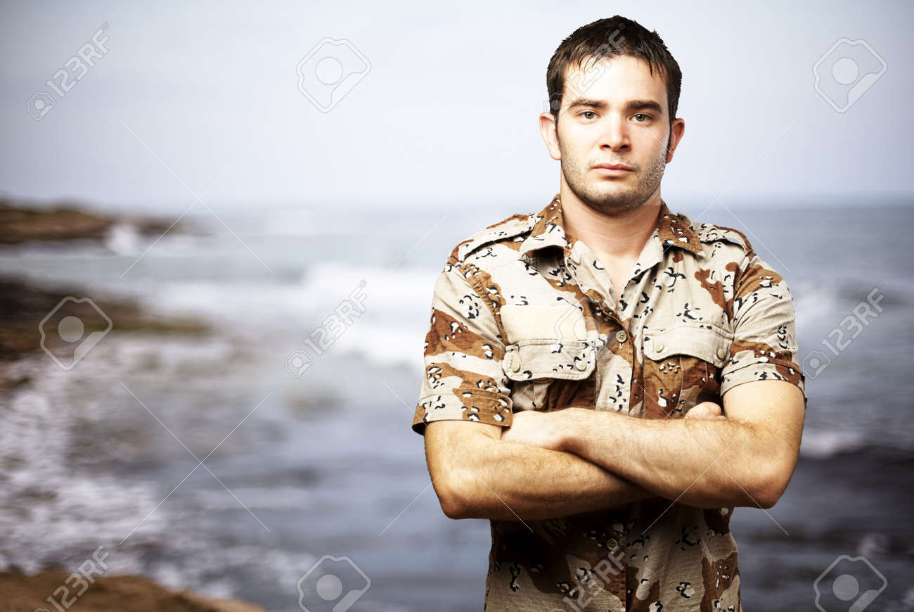 portrait of a serious young soldier standing against a sea background Stock Photo - 12656349