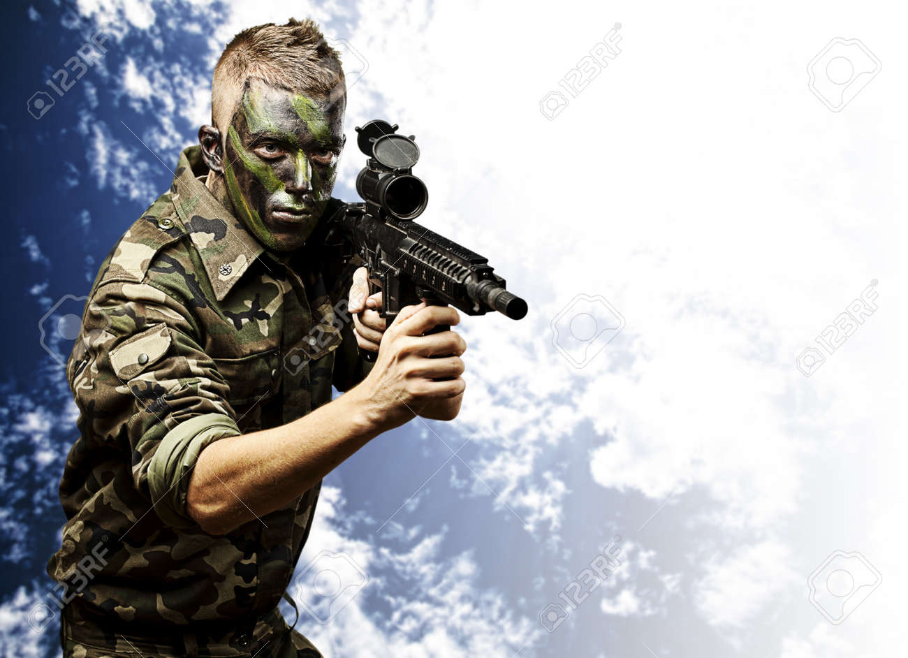 portrait of young soldier pointing with rifle against a blue sky background Stock Photo - 12656291