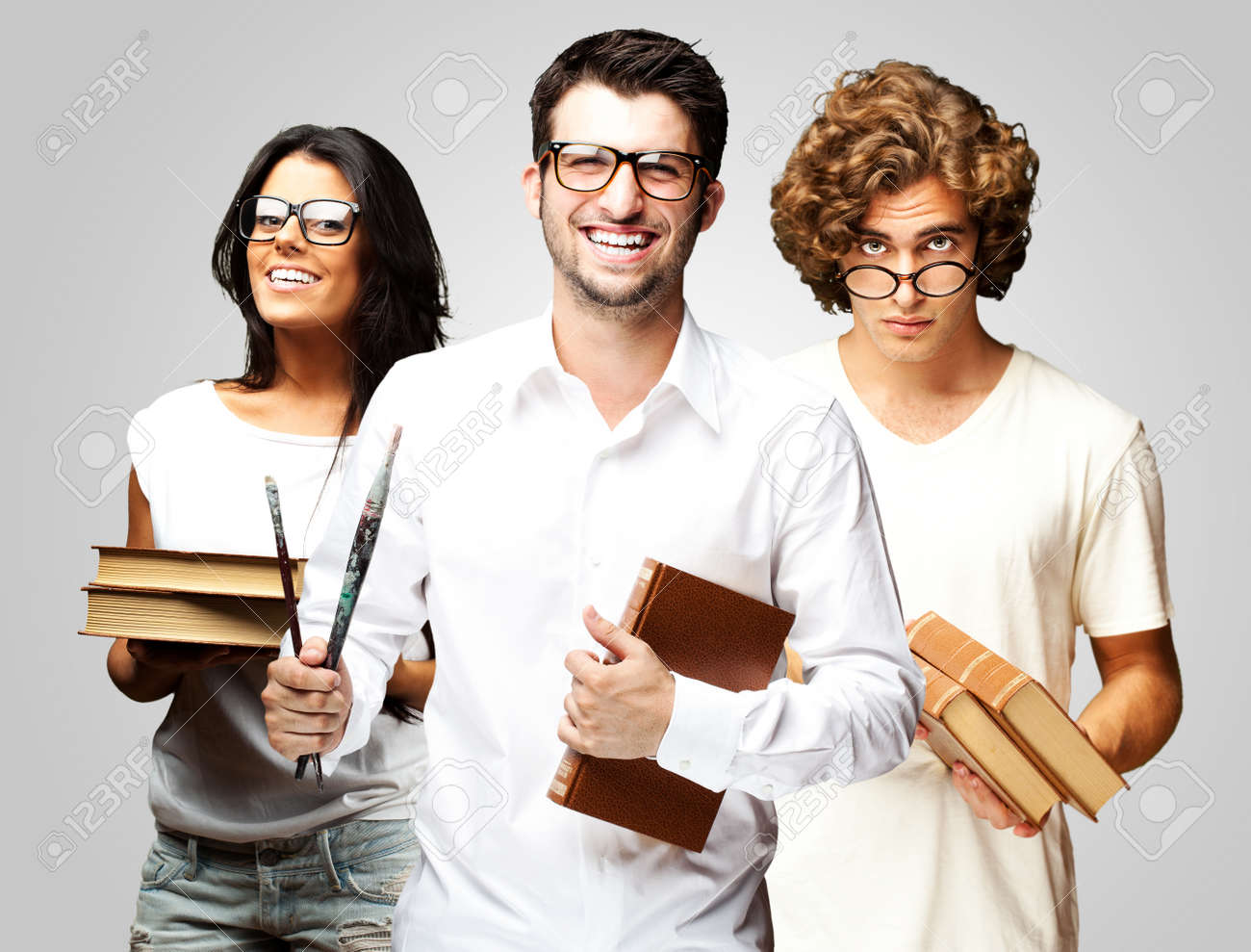 portrait of young students holding books over grey background Stock Photo - 12656305