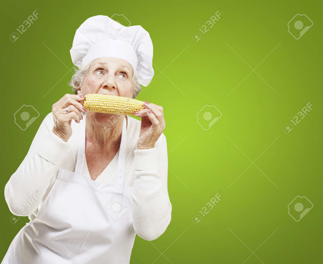 senior woman cook eating a corncob against a green background Stock Photo - 12656438