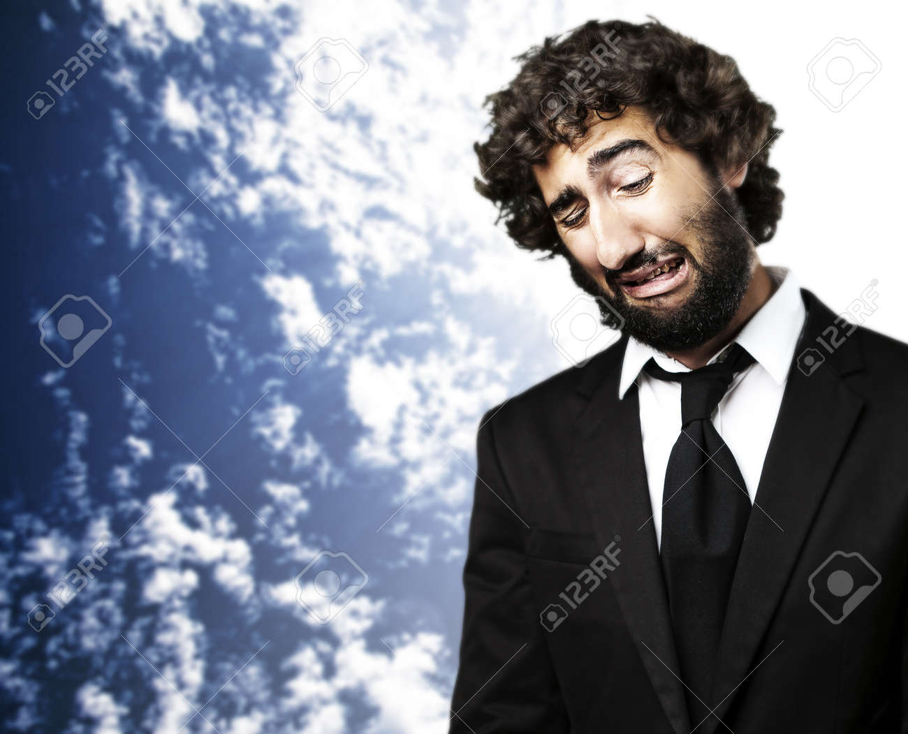 portrait of young business man with suit crying against a blue sky background Stock Photo - 12656757