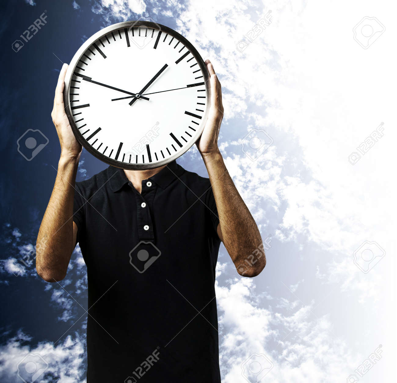 portrait of young man holding a clock with his hands against a cloudy sky background Stock Photo - 12656781