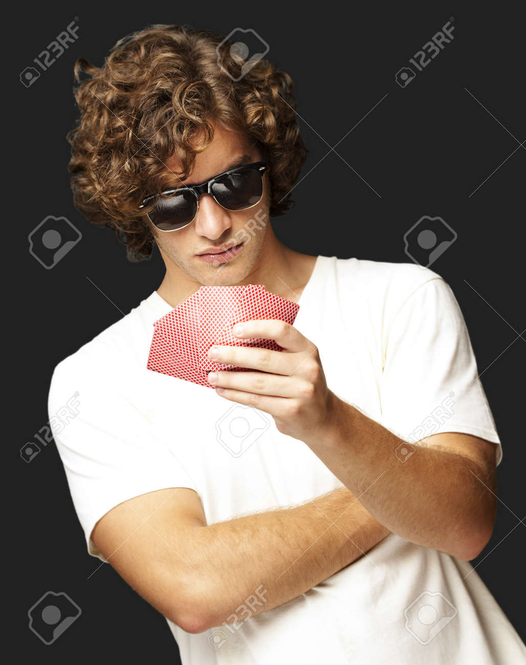 young man holding cards and wearing sunglasses against a black background Stock Photo - 13486247