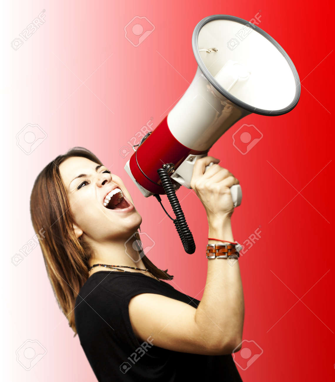 portrait of young girl shouting with megaphone over red background Stock Photo - 12656541