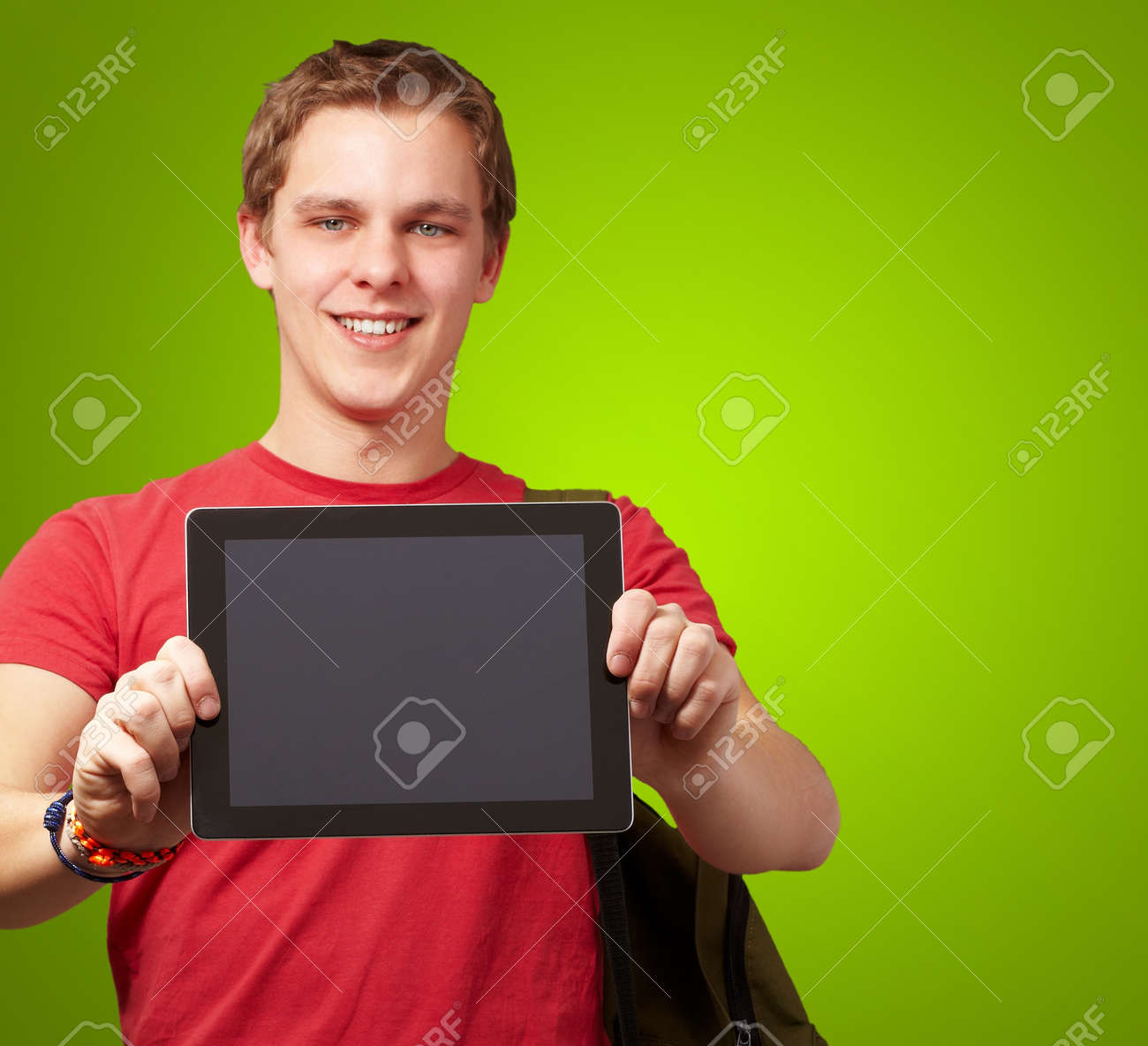 portrait of young man holding a digital tablet over green background Stock Photo - 12656543