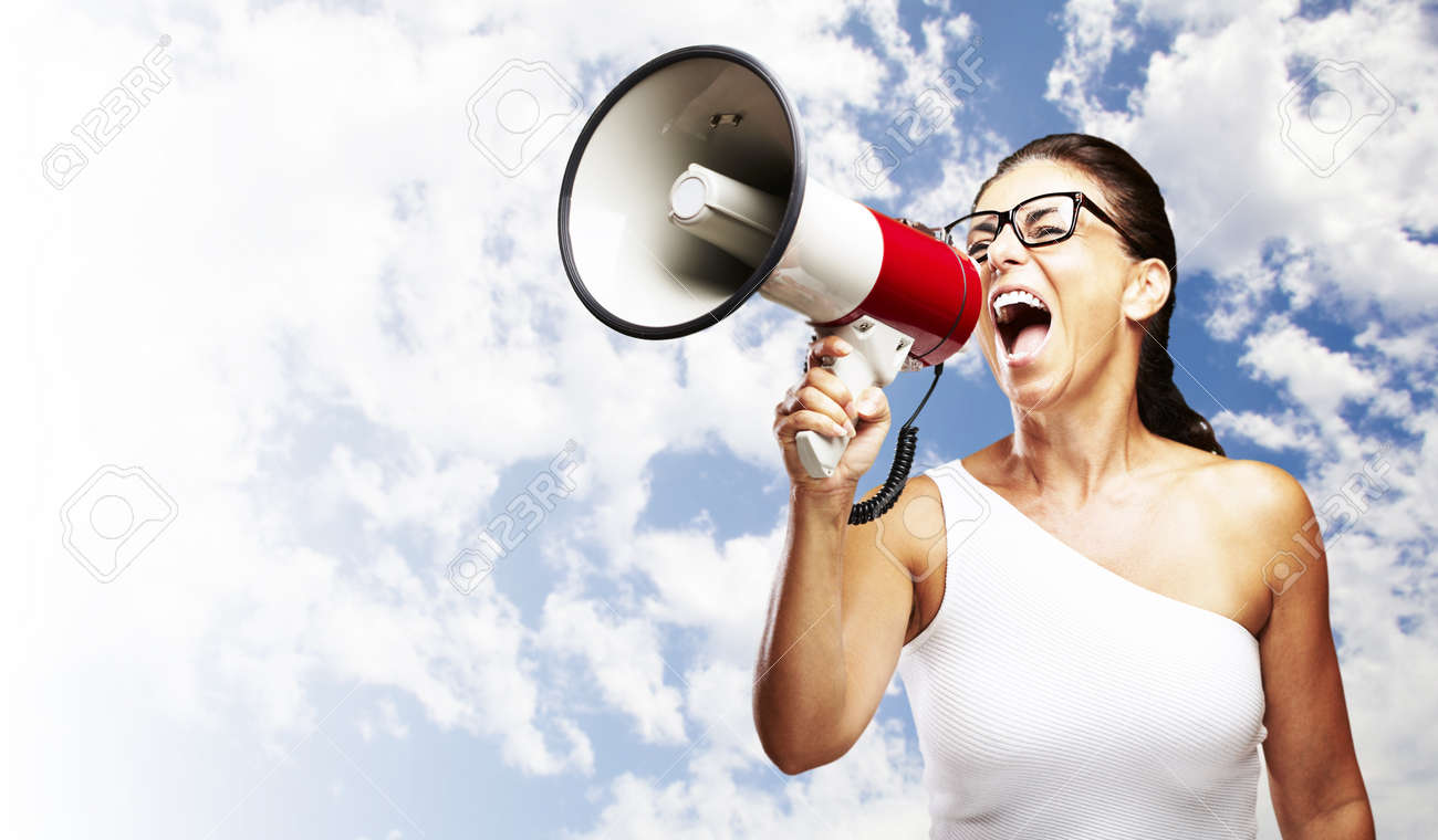 portrait of middle aged woman shouting with megaphone against a cloudy sky Stock Photo - 12656722