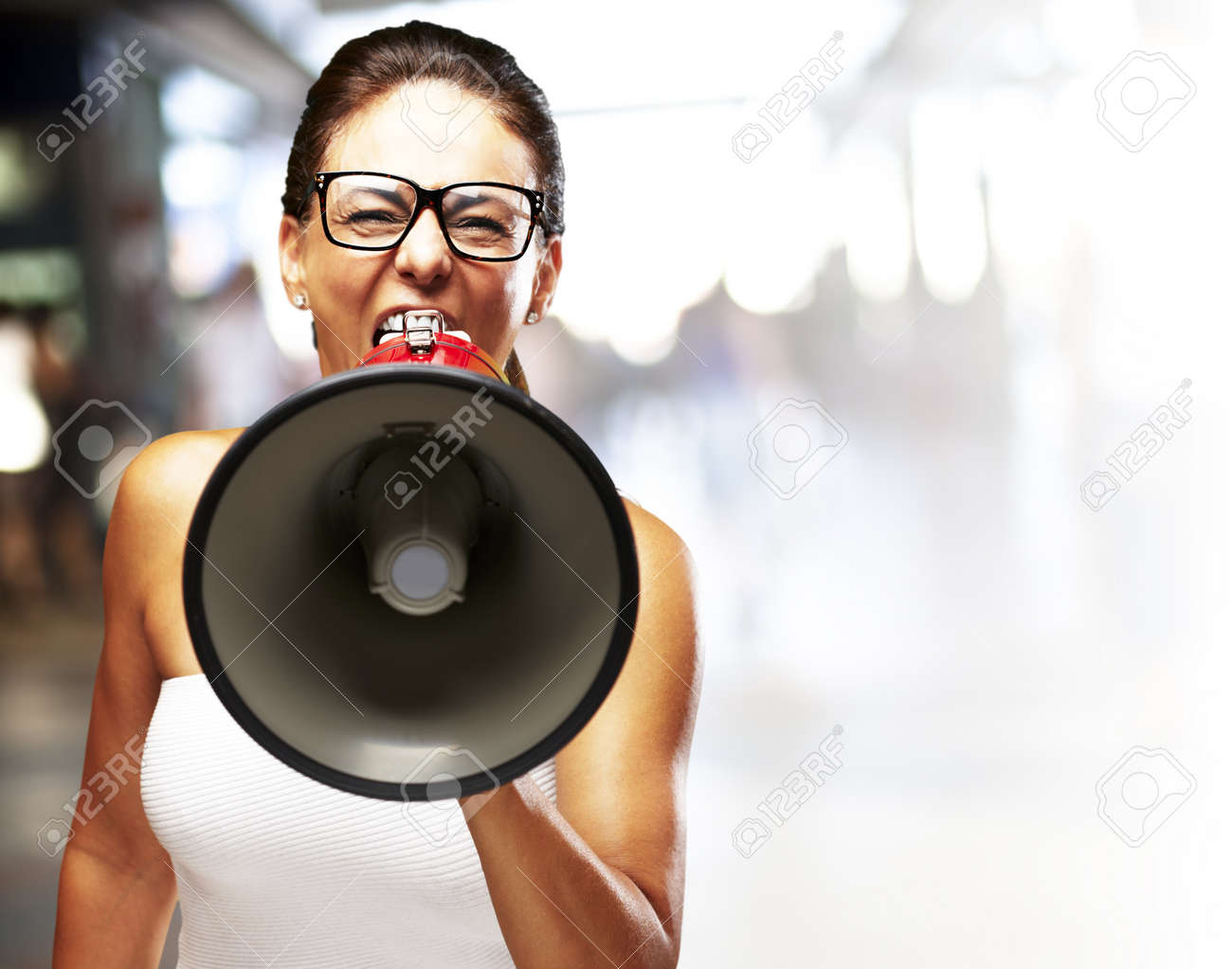 middle aged woman shouting with megaphone at a busy place Stock Photo - 12656679