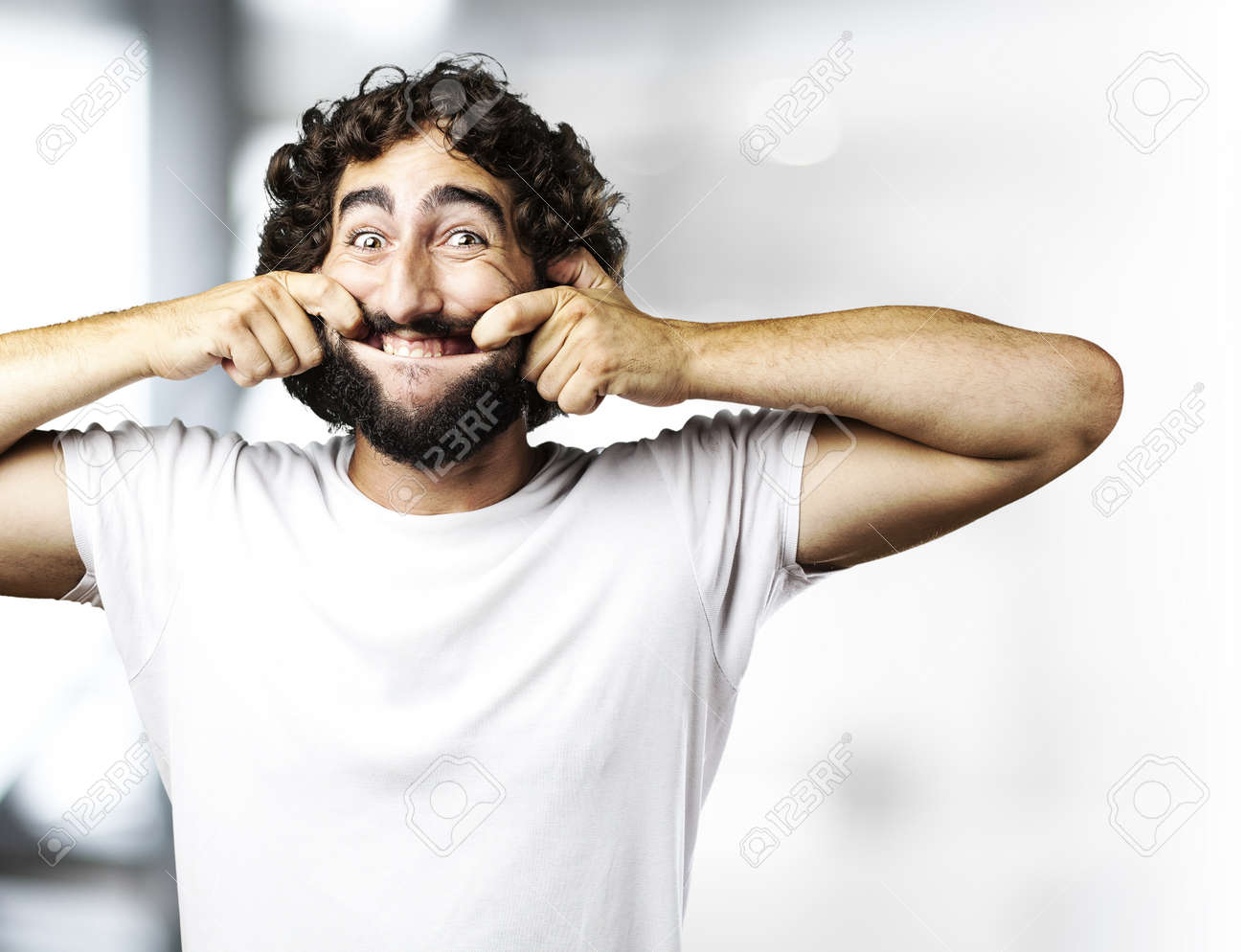 portrait of young man pulling his mouth smiling indoor Stock Photo - 13156544
