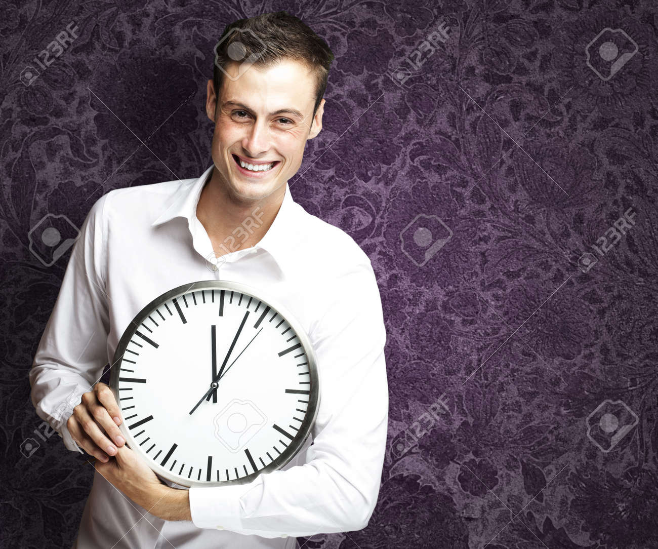 portrait of young man holding clock against a vintage background Stock Photo - 13156602