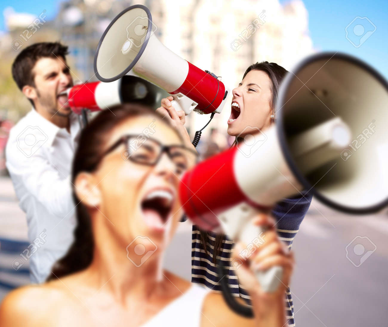 young friends screaming with megaphone against a building Stock Photo - 13156536