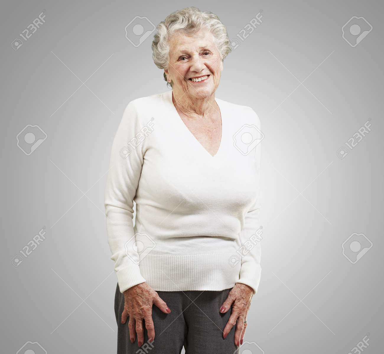 pretty senior woman smiling against a grey background Stock Photo - 13156585