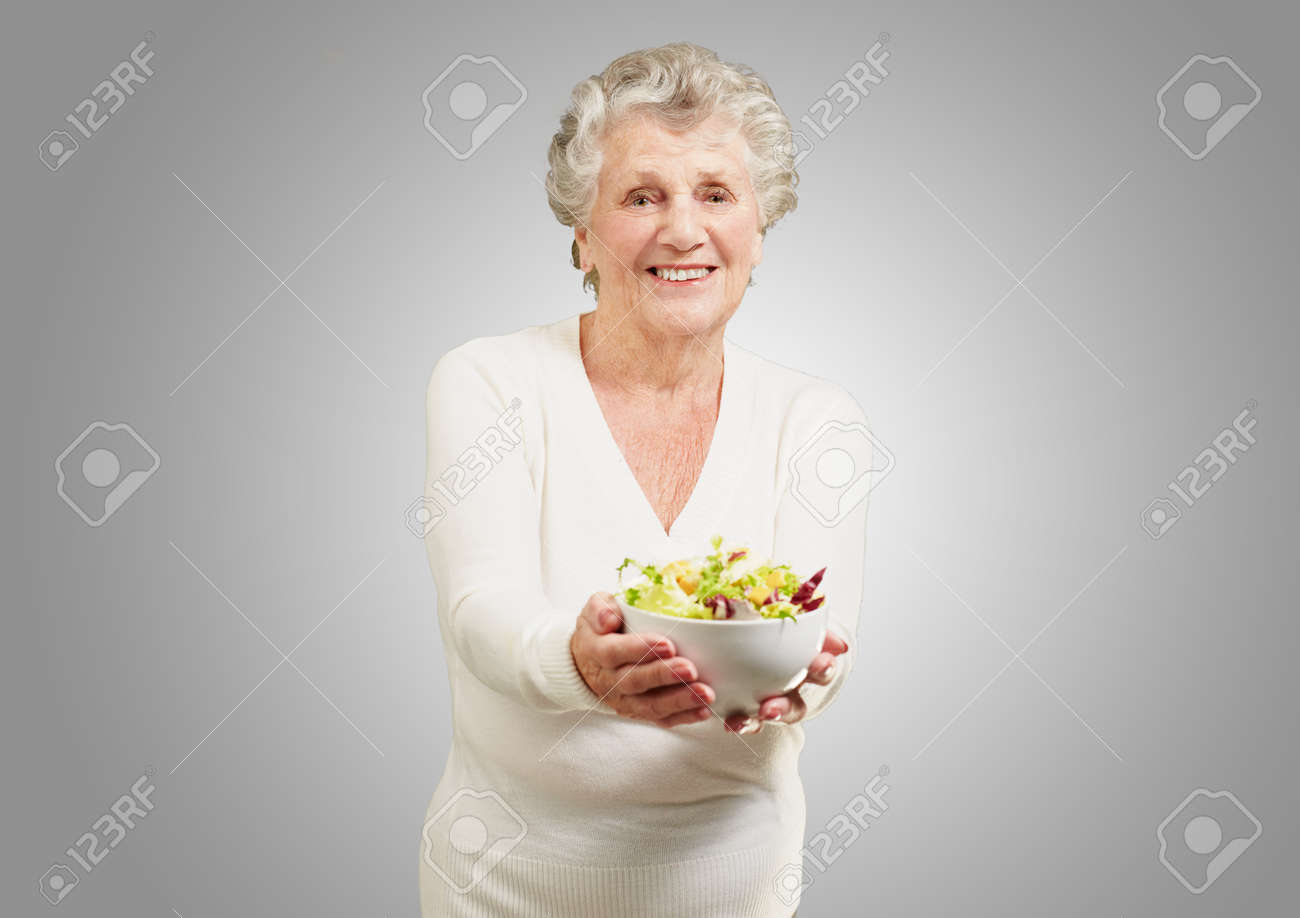 portrait of senior woman showing a fresh salad over grey background Stock Photo - 13156605
