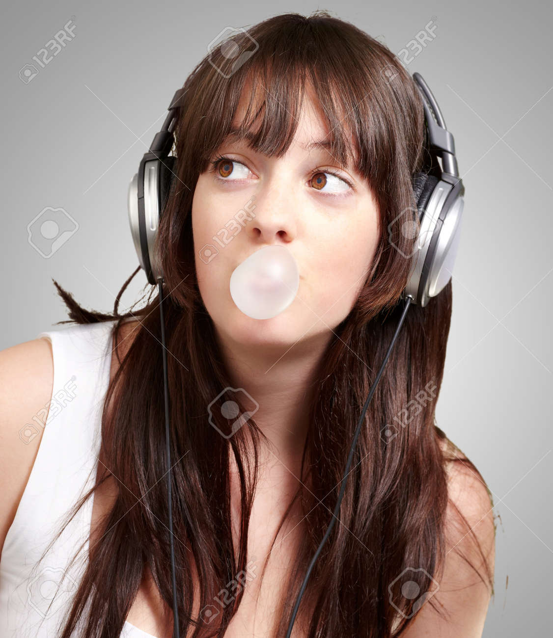 portrait of young woman listening to music with bubble gum over grey background Stock Photo - 13280534