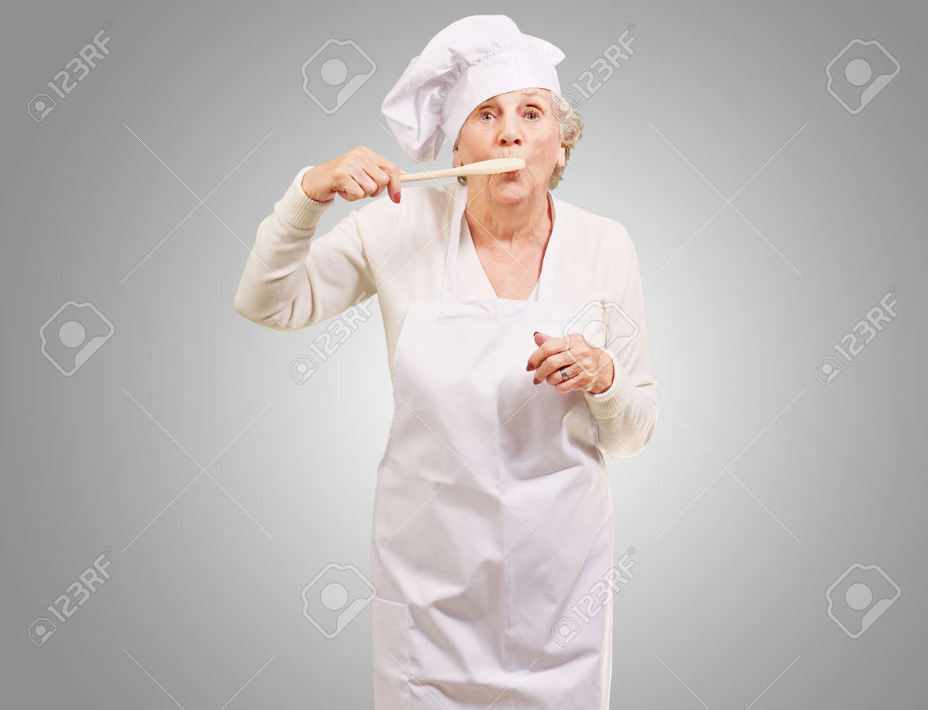 portrait of cook senior woman with wooden spoon on mouth over grey Stock Photo - 13280508