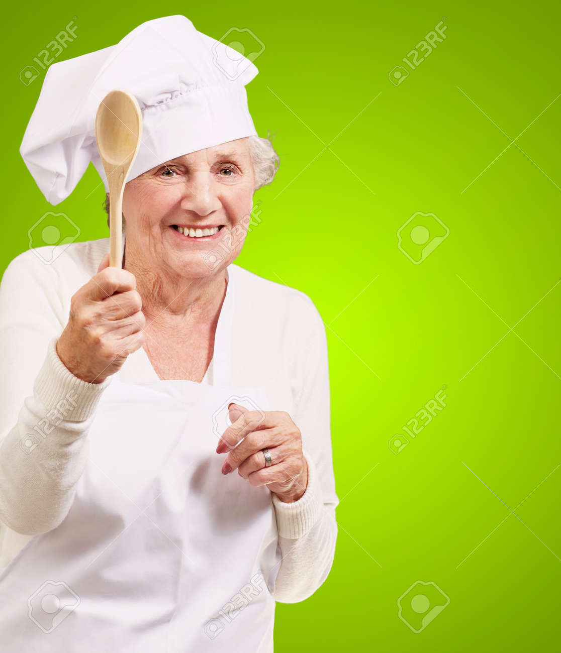 portrait of senior cook woman holding a wooden spoon over green background Stock Photo - 13280082