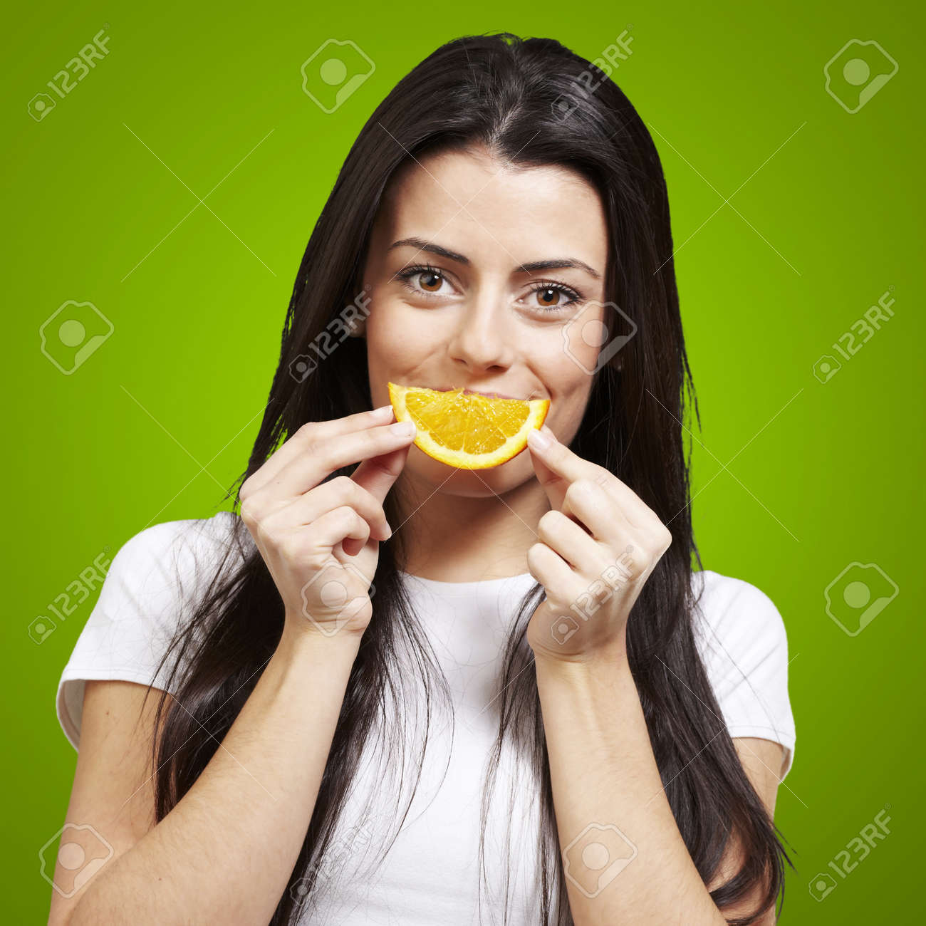 woman with an orange slice as a smile against a green background Stock Photo - 13280124