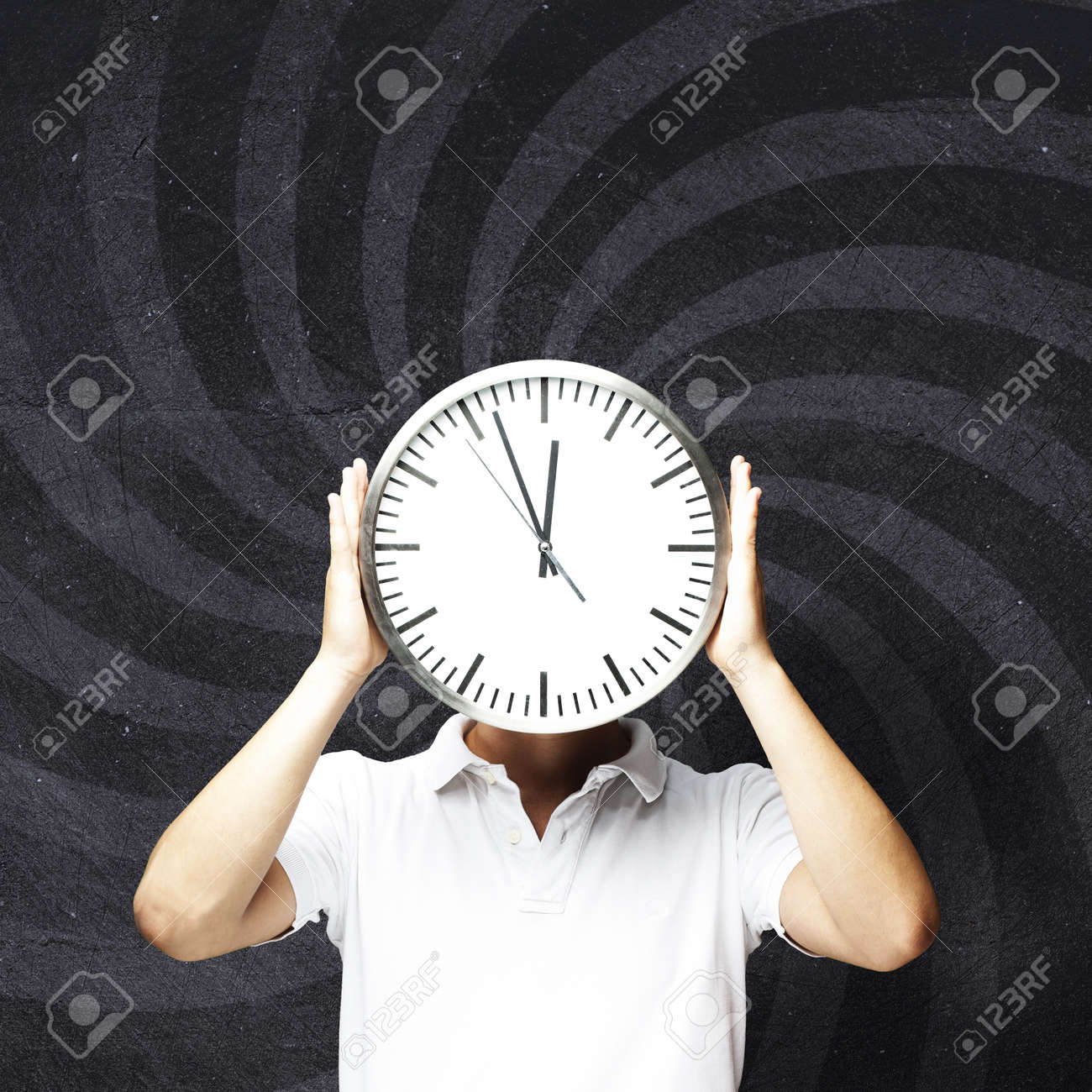 young man hiding his face behind a clock against an abstract background Stock Photo - 13485741