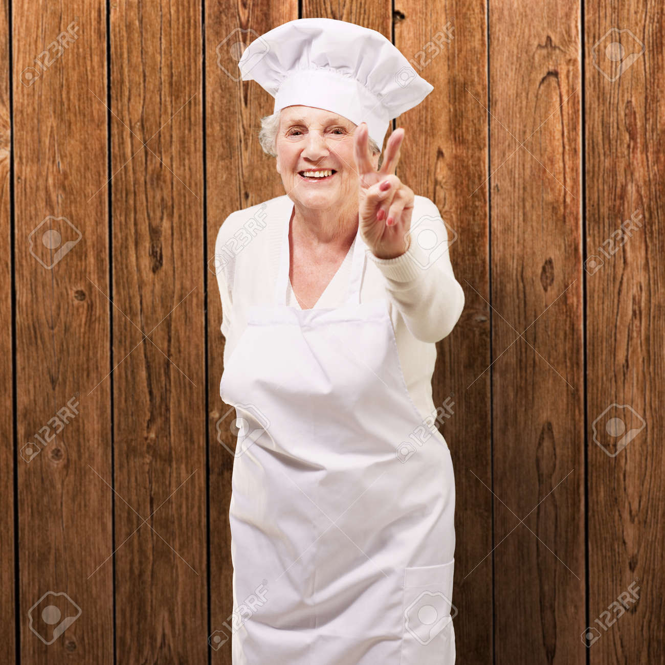 portrait of cook senior woman doing good gesture against a wooden wall Stock Photo - 13280215