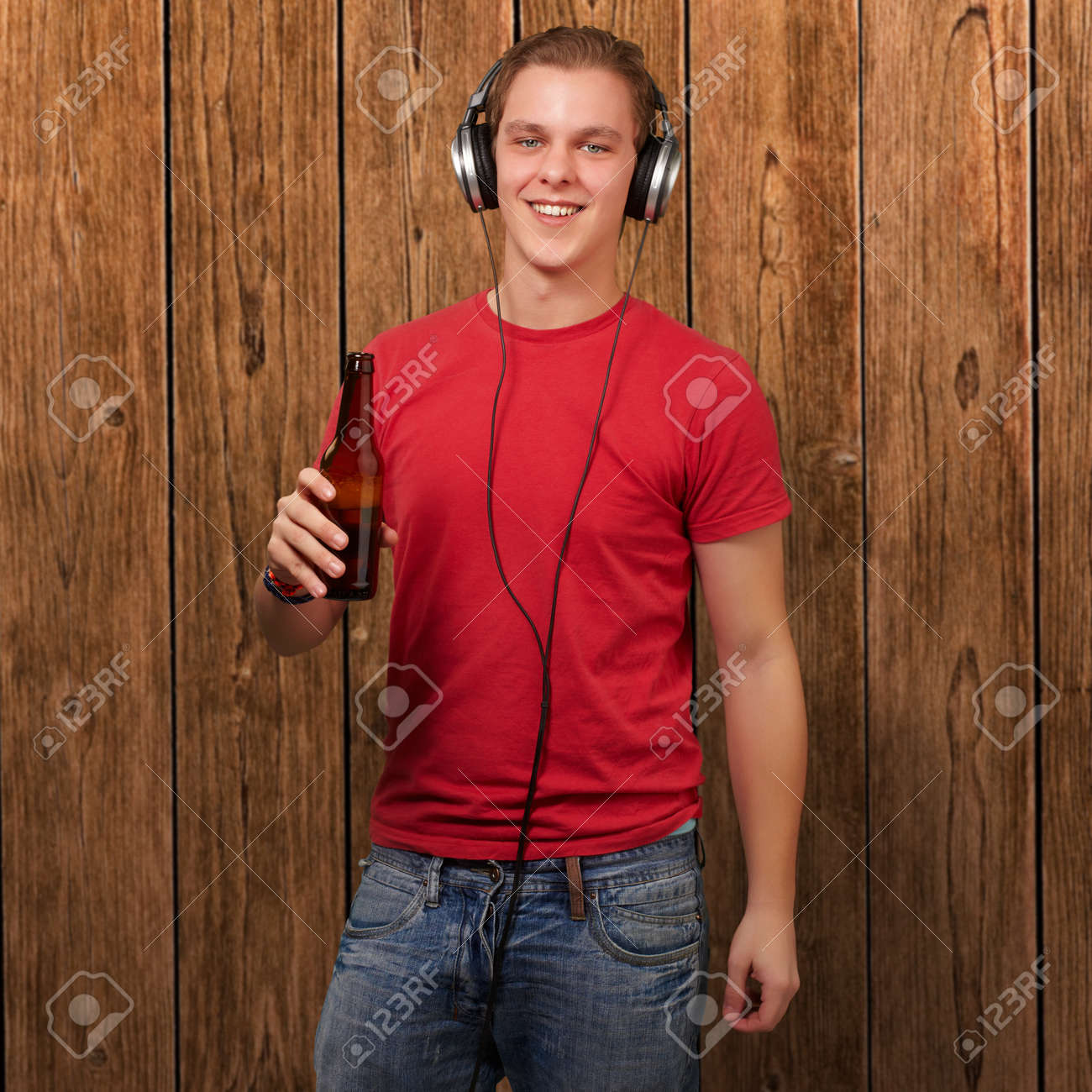 portrait of young man listening music and holding beer against a wooden wall Stock Photo - 13280246
