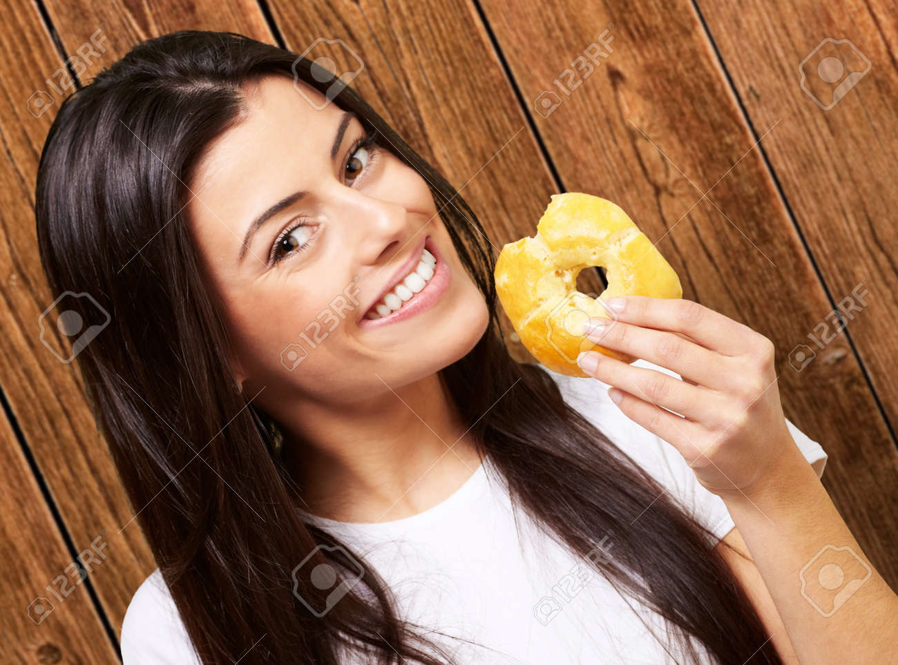portrait of young woman eating a donut against a wooden wall Stock Photo - 13280352