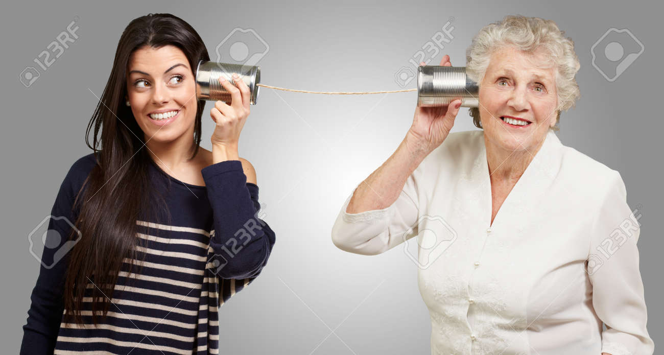 portrait of young girl and her grandmother hearing sounds using a metal tin can Stock Photo - 13280305