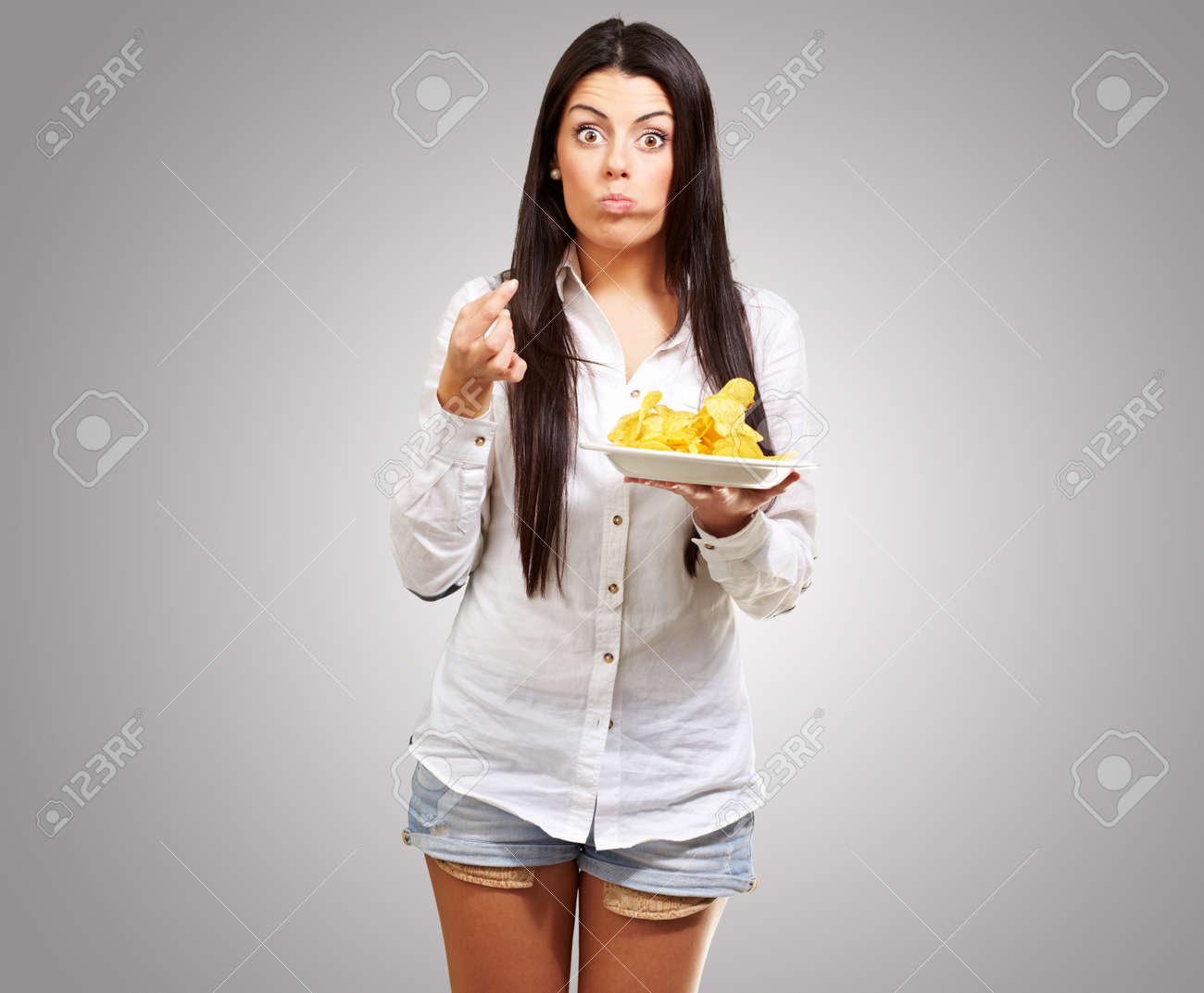young woman eating potatoe chips against a grey background Stock Photo - 13280263