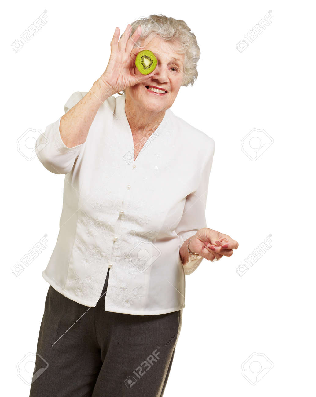 portrait of senior woman holding kiwi in front of her eye over white background Stock Photo - 13608632