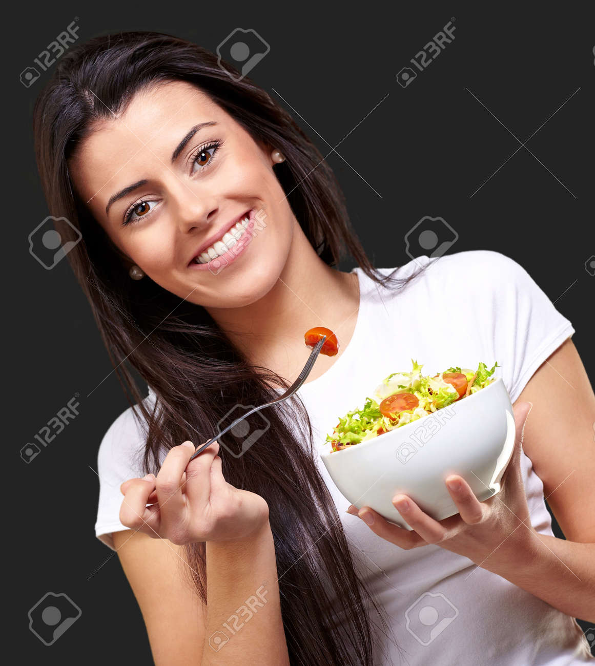 portrait of healthy woman eating salad against a black background Stock Photo - 13844766